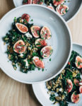 A nutty toasted farro salad featuring al dente farro tossed with massaged kale, ruby-hued fresh figs, creamy goat cheese crumbles, and fresh parsley.