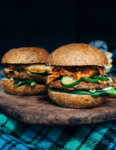 A fresh spin on the traditional tailgating party featuring plant-based kimchi burgers topped with grilled green onions and a spicy gochujang sunflower spread.