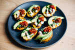 These vegetarian Tex-Mex potato skins are loaded with pinto beans, cheddar, green onions, herbs, jalapeños, avocado, and lime crema.