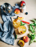 Peach bourbon smash cocktails infused with fresh basil leaves are bright, lemony, and the perfect way to enjoy sweet summer peaches.