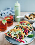 These quick and easy grilled chicken tacos start with a vibrant orange and lime juice marinade, and are layered with avocado-lime sauce, and a simple red cabbage and radish slaw.