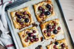 Sweet and savory brie and roasted grape tarts with a drizzle of honey, fresh thyme, and black pepper are the perfect simple-yet-decadent holiday appetizer.